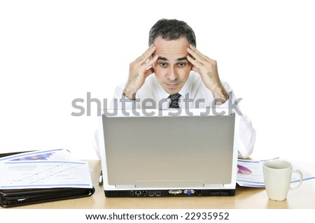 Stressed businessman sitting at his desk isolated on white background - stock photo