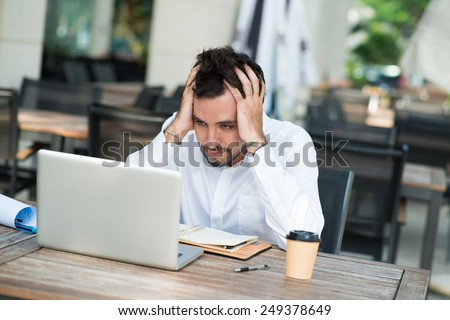 Stressed businessman sitting in front of laptop in the cafe - stock photo
