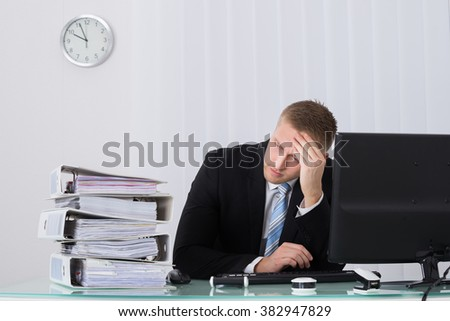 Stressed Businessman Sitting In Office With Hand On Head