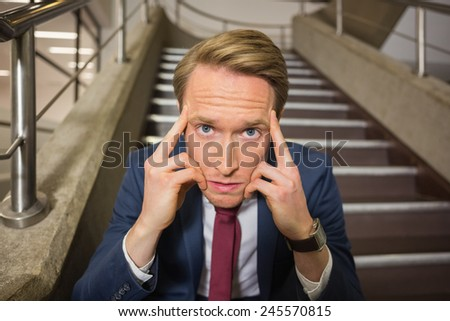 Stressed businessman sitting on steps in office building - stock photo
