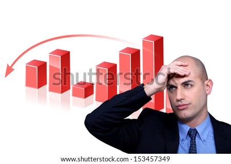 Stressed businessman standing by bar chart - stock photo