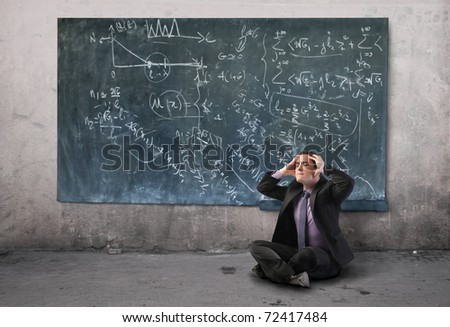 Stressed businessman suffering from headache with blackboard on the background - stock photo