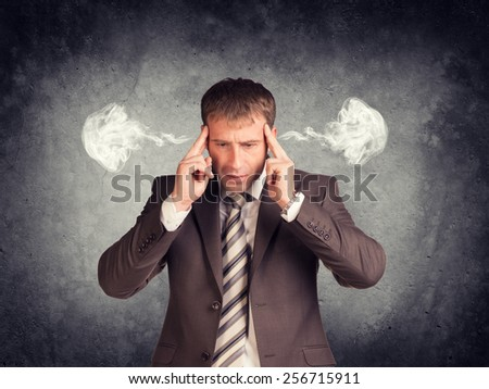 Stressed businessman thinking with his fingers on his temples, smoke from his ears. Raw concrete wall as backdrop