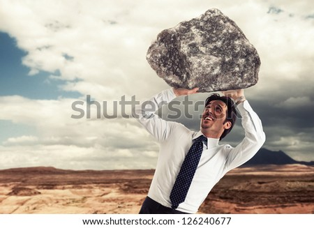 Stressed businessman trying to lift a rock