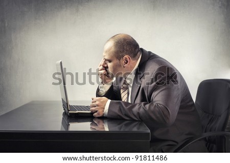 Stressed businessman using a laptop - stock photo