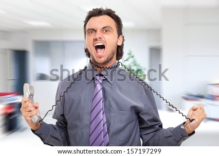 Stressed businessman using the phone cord to strangle himself - stock photo