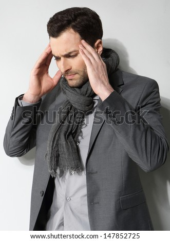 Stressed businessman with a headache on a gray background