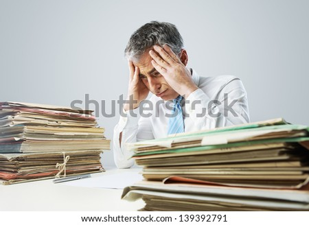 Stressed businessman, with a too much paperwork and files piled up on the table - stock photo
