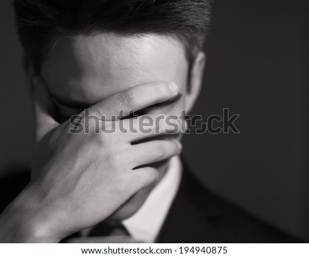 Stressed businessman with hand over his face. Unrecognizable person. - stock photo