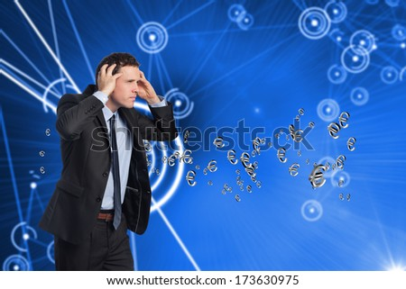 Stressed businessman with hands on head against futuristic glowing circles