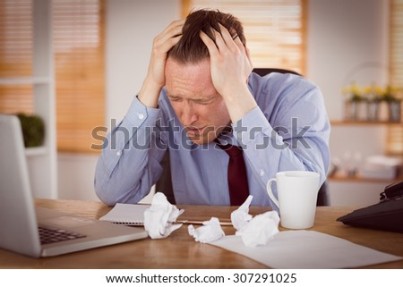 Stressed businessman with head in hands at office