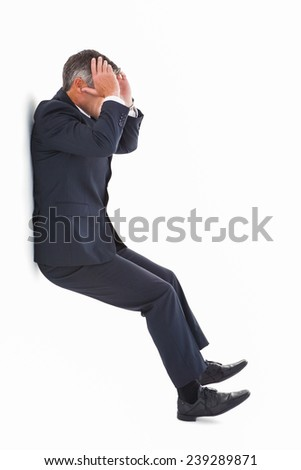 Stressed businessman with head in hands on white background