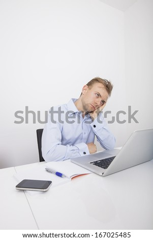 Stressed businessman with laptop sitting at desk in office - stock photo