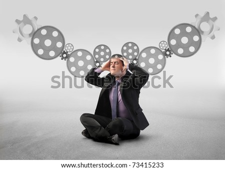 Stressed businessman with mechanisms on the background - stock photo