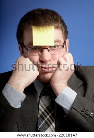 Stressed businessman with yellow sticky note on forehead - stock photo