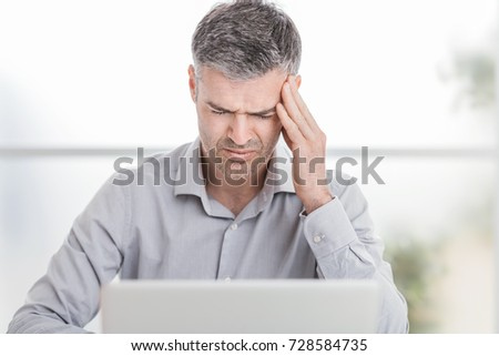 Stressed businessman working at office desk and having an headache, he is touching his temples
