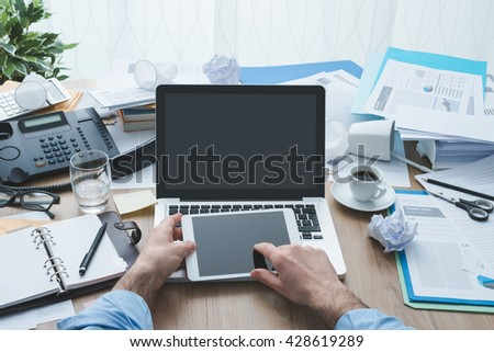 Stressed businessman working in the office and using a tablet, his desk is messy and cluttered, productivity and deadlines concept, point of view shot