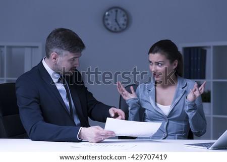 Stressed businesswoman and her angry boss sitting in office at night