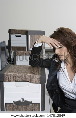 Stressed businesswoman and moving boxes at office desk - stock photo