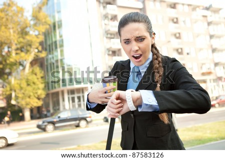 stressed businesswoman checking the time, outdoor - stock photo