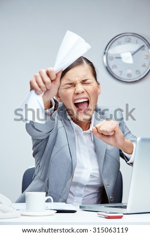 Stressed businesswoman with creased paper shouting at workplace - stock photo