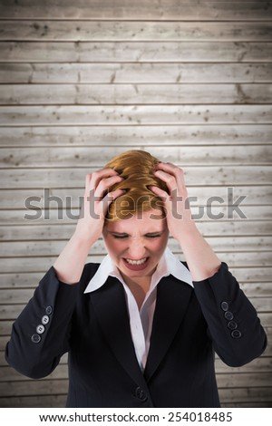Stressed businesswoman with hands on her head against wooden planks background - stock photo