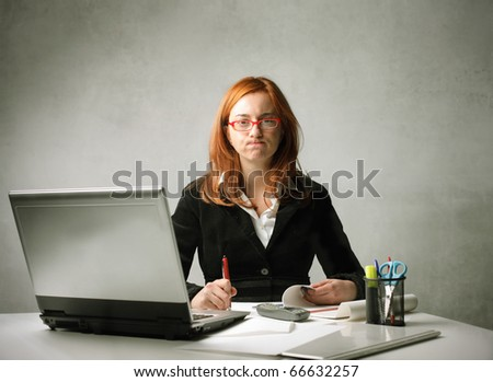 Stressed businesswoman working at her desk in front of a laptop - stock photo