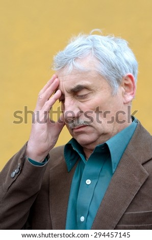 Stressed caucasian senior man with headache put his hand on his forehead, frowning, looking down. Head and shoulders portrait. Brown corduroy jacket, green shirt, solid yellow background.