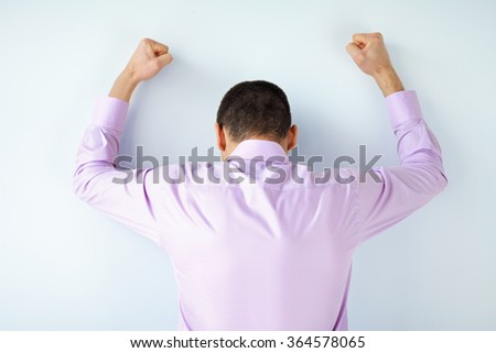 Stressed despair business man punching the wall - stock photo