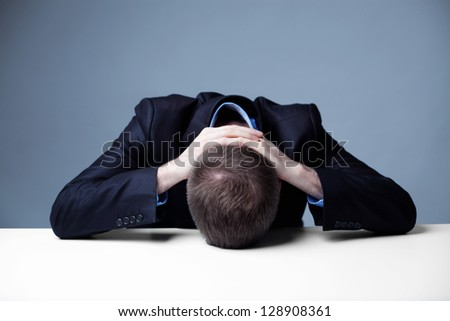 Stressed employee with head on a table. - stock photo