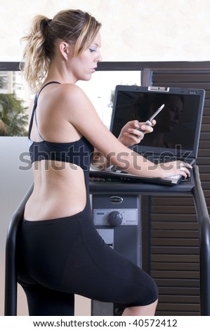 stressed executive woman in the gym with lap top and phone - stock photo