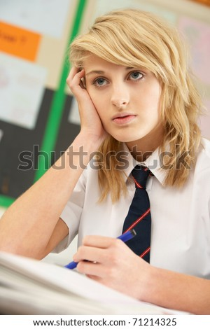 Stressed Female Teenage Student Studying In Classroom - stock photo