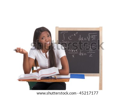Stressed High school or college ethnic African-American female student sitting by the desk at math class. Blackboard with complicated advanced mathematical formals is visible in background