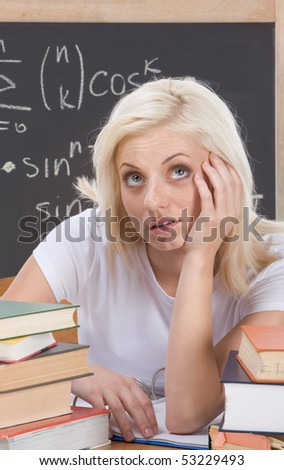 Stressed High school or college female student sitting by the desk at math class. Blackboard with complicated advanced mathematical formals is visible in background - stock photo