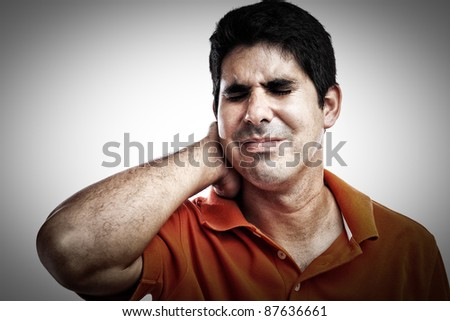 Stressed hispanic man suffering from pain in his neck and back - stock photo