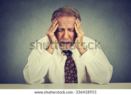 Stressed hopeless elderly business man in depression sitting at the office table isolated on gray wall background. Overworked worried senior employee - stock photo