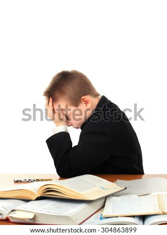 Stressed Kid at the School Desk with a Books Isolated on the White Background - stock photo