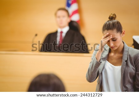 Stressed lawyer with head bowed in the court room - stock photo