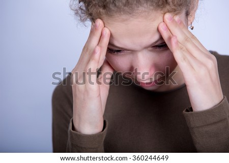 Stressed little girl having problems.Portrait of  little girl suffering from headache and holding hands on her head. - stock photo