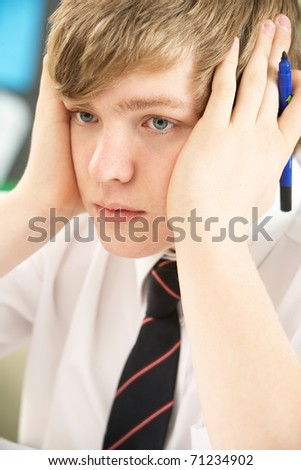 Stressed Male Teenage Student Studying In Classroom - stock photo
