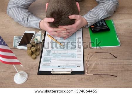 stressed man filling 1040 tax form - stock photo