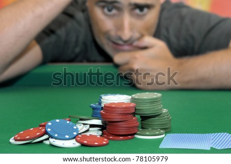 Stressed man in a poker table gambling - stock photo