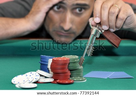 Stressed man in a poker table gambling his house - stock photo