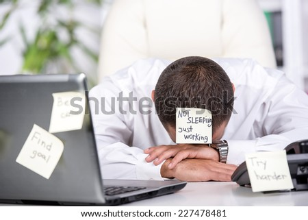 Stressed man is looking online for a job. Many stickers on it. - stock photo