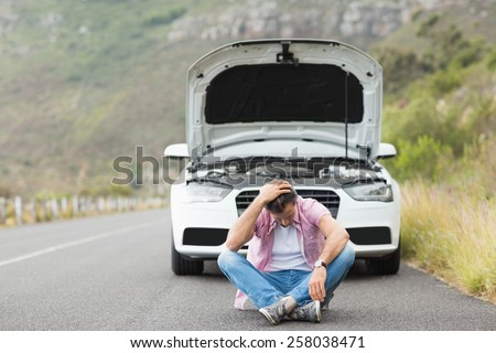 Stressed man sitting after a car breakdown at the side of the road - stock photo