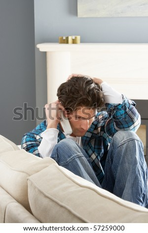 Stressed Man Sitting On Sofa At Home Talking On Phone - stock photo