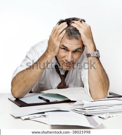 Stressed man slumping over his desk covered with bills and overdue notices.