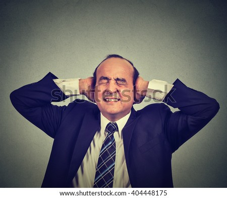 Stressed man upset frustrated has too many thoughts headache isolated on gray wall background  - stock photo