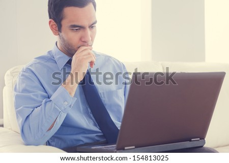 Stressed man using a laptop sitting on a sofa in living room at home