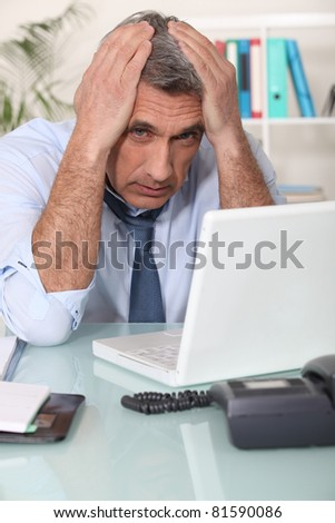 Stressed man using laptop - stock photo